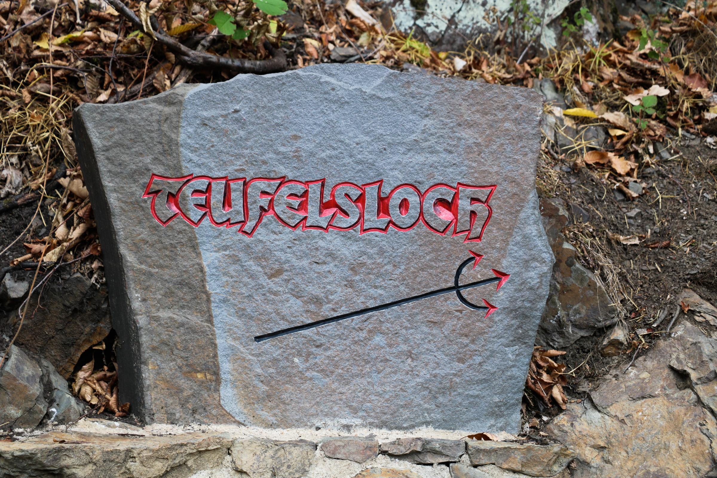 Ein Stein, auf dem das Wort Teufelsloch eingraviert ist, darunter ein Dreizack.
