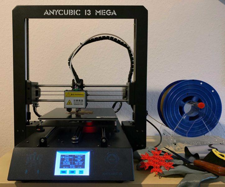 Ein großes schwarzes Gestell, vorne ein Display. Der Drucker druckt gerade. Nebendran eine Rolle mit Filament.
