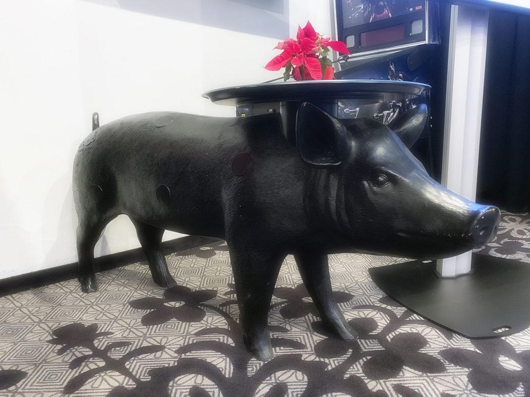 Ein großes schwarzes Deko-Schwein mit Platte auf dem Kopf, auf der wiederum ein kleiner Topf mit roten Blumen steht.