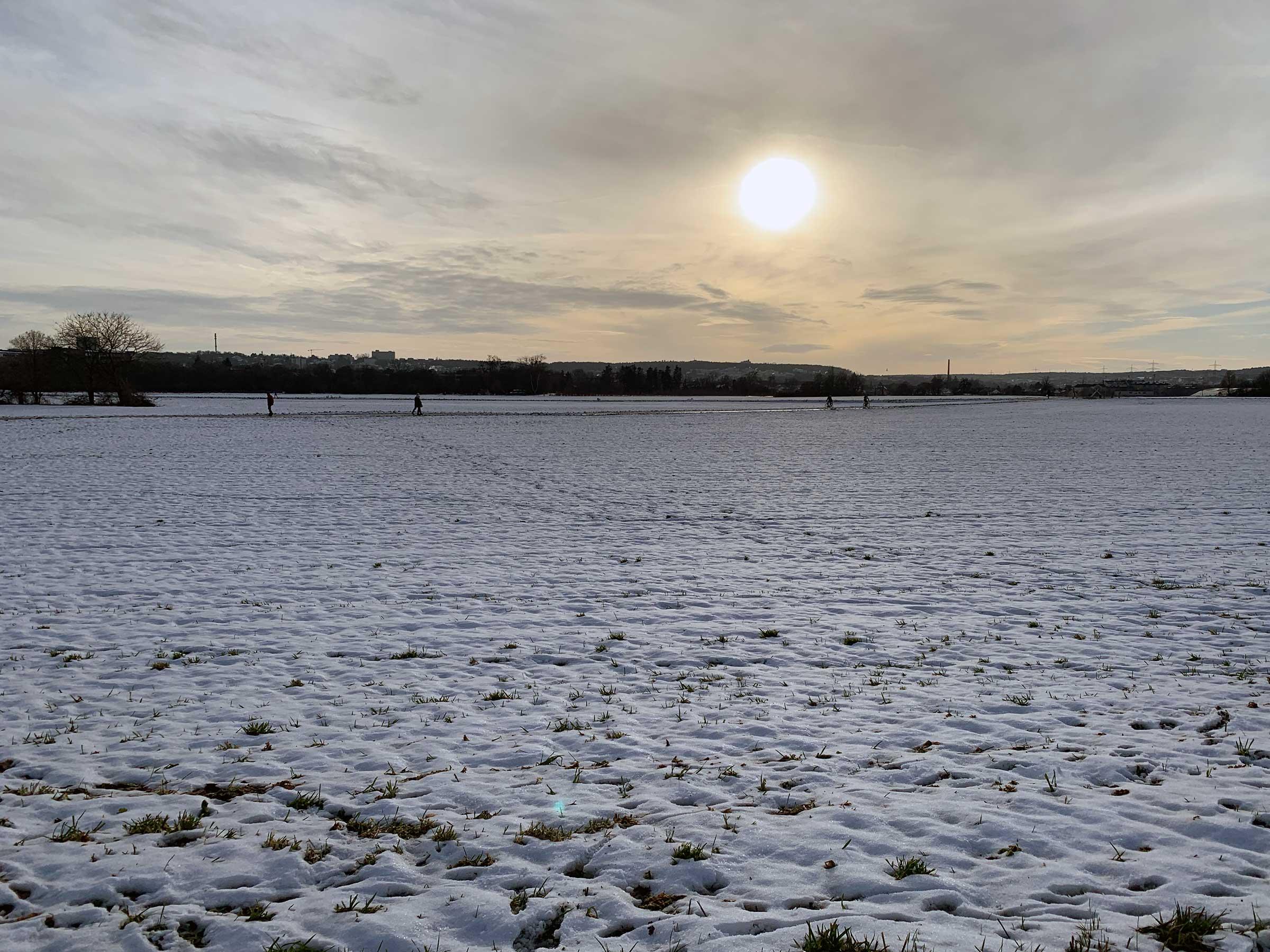 Ein schneebedeckter Acker, im Hintergrund ganz klein Menschen, darüber leicht diesig die untergehende Sonne.
