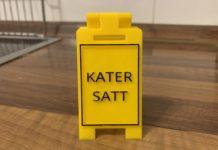"""Ein gelber Aufsteller, auf dem in schwarzer Schrift und schwarzem Rahmen """"Kater satt"""" steht."""