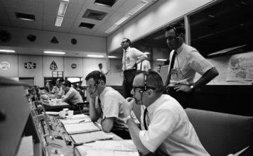 Männer im Look der 1960-er mit Headsets sitzen an einem Schaltpult bzw. stehen dahinter. Sie alle blicken in die gleiche Richtung aus dem Bild hinaus.