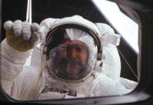 Ein Astronaut im Weltall klopft von außen an das Fenster.