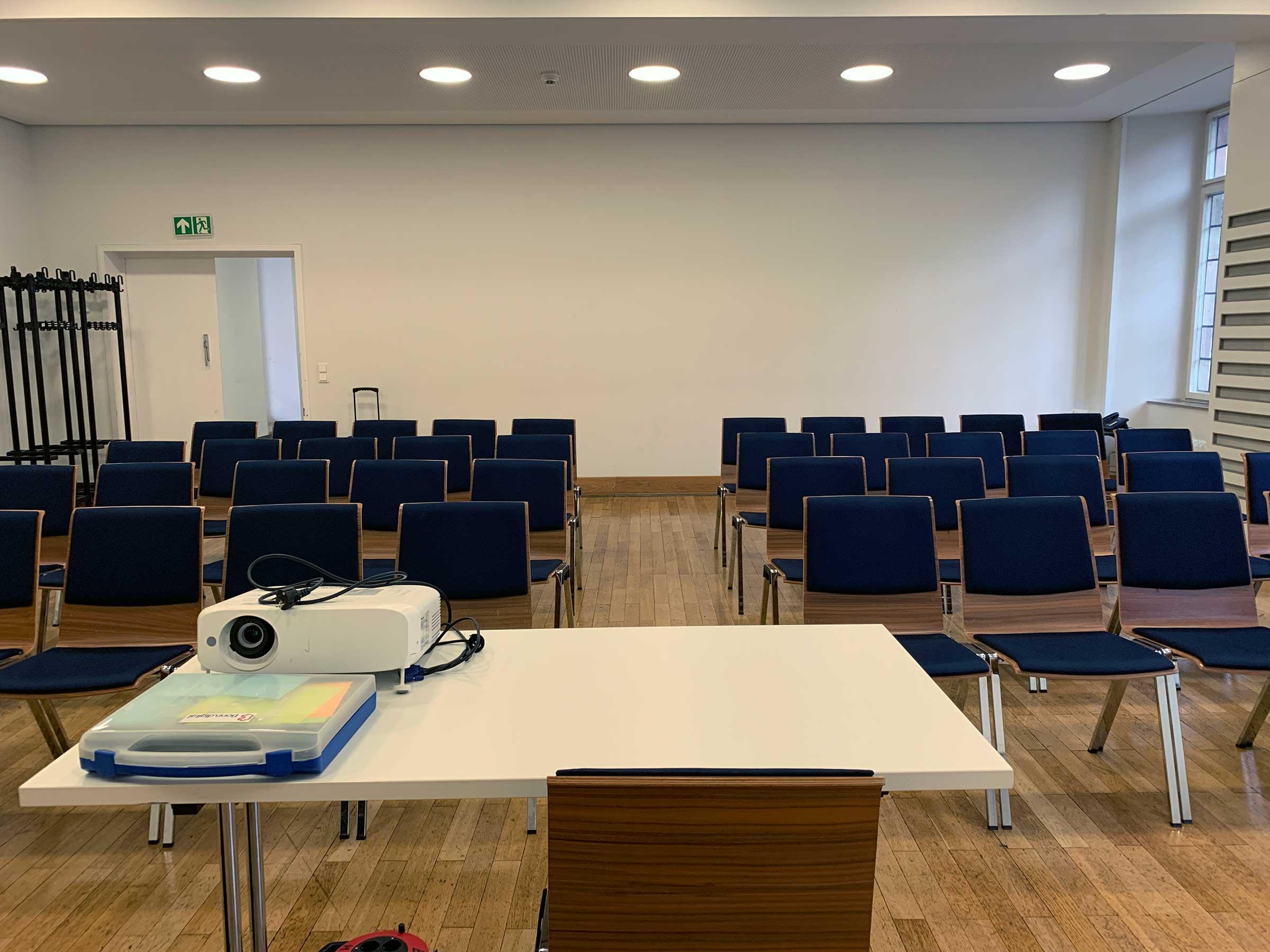 Ein kleinerer Saal mit zwei Blöcken Stuhlreihen von vorne gesehen. Ganz vorne ein Tisch mit einem Beamer und einem Moderationskoffer drauf.