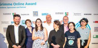 Mehrere Menschen vor einer Grimme-Online-Award-Fotowand. Anne hält den gläsernen Preis, Johannes steht links, Ralph Ruthe macht Faxen im Hintergrund.