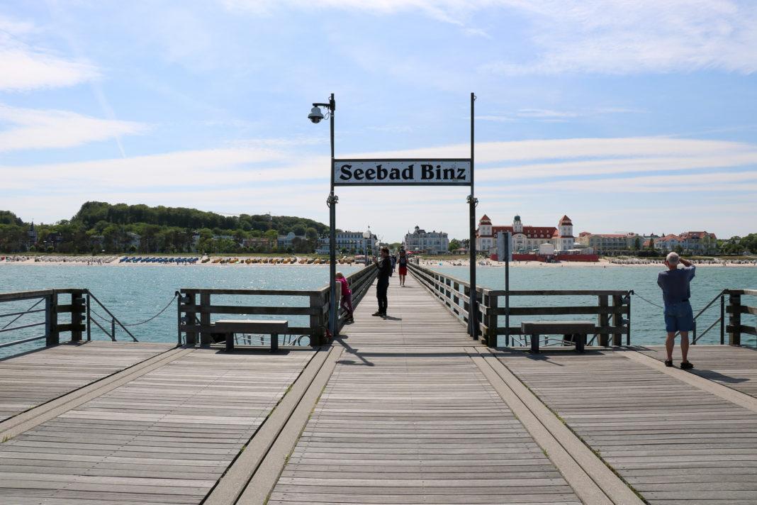 Blick vom Ende einer langen Seebrücke zurück aufs Land, im Hintergrund große Häuser, einige mit Türmen. Im Vordergrund, über der Brücke, ein großes Schild: Seebad Binz.
