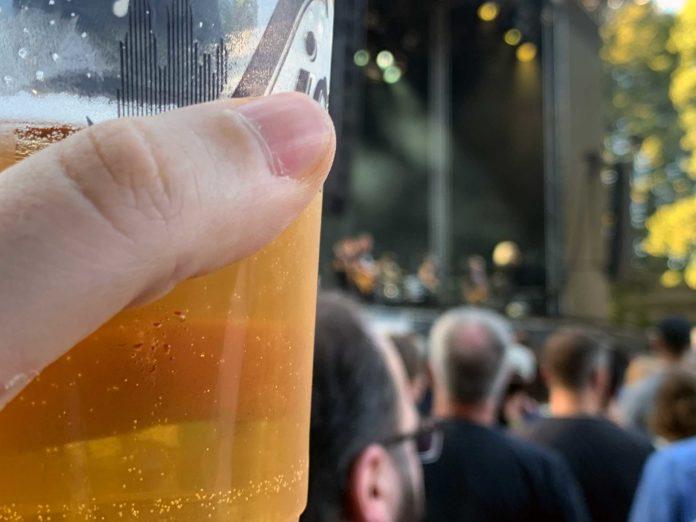 Ein fast voller Bierbecher, der in einer Hand gehalten wird. Im Hintergrund verschwommen erkennbar eine Musikbühne und viele Menschen.