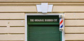 Eine Hausfasade mit einem geschlossenen grünen Rolltor, darüber ein Schild: The Original Barber Cut