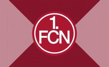 """Das Wappen des 1. FC Nürnberg (roter Kreis, darauf in weißer schnörkelloser Schrift in der ersten Zeile """"1."""", in der zweiten Zeile """"FCN""""."""