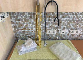 Bild aus dem Kreißsaal: Vom Hängeschrank hängen ein Maßband und ein Stethoskop, unterhalb eine Wickelauflage mit bereitgelegten Klamotten für das Baby und einem Handtuch.