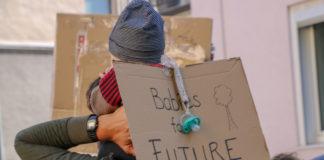 """Ein Vater ist von hinten zu sehen, der sein Baby auf den Schultern trägt. Es hat ein Schild umgebunden, auf dem """"Babies for future"""" steht und von dem ein Schnuller baumelt."""