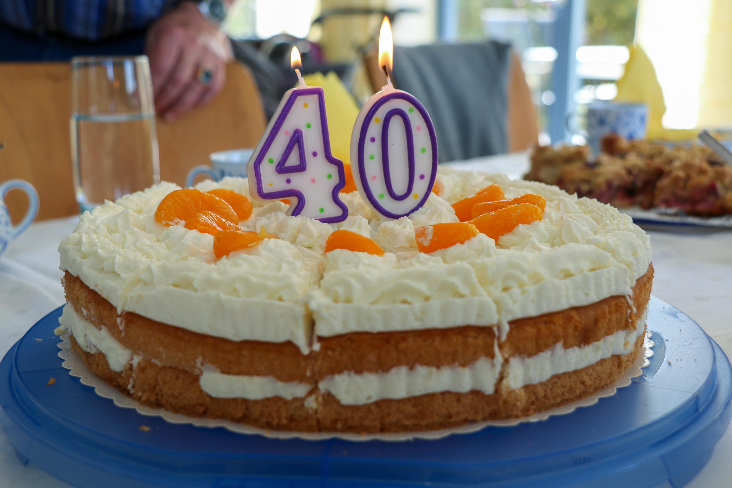 Eine Torte mit zwei brennenden Kerzen in der Mitte, eine 4 und eine 0.