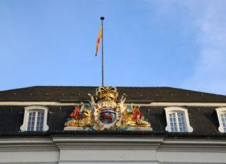 Foto vom Dach des Rathauses Bonn mit dem Stuck-Wappen und der Bonner Flagge darüber