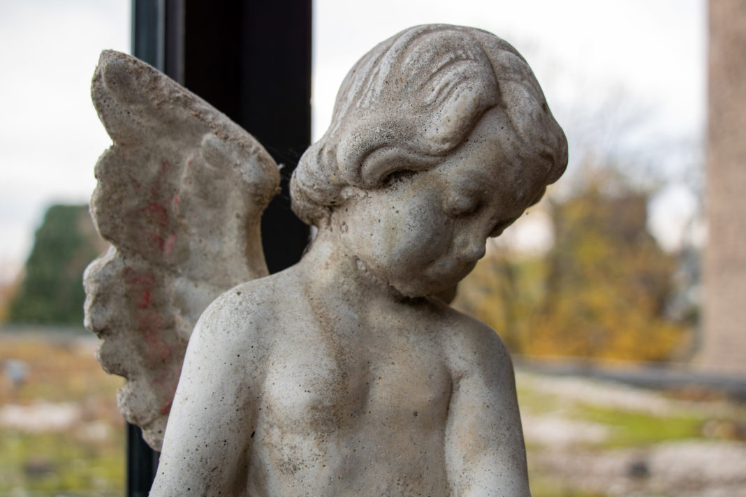 Eine kleine Statue eines Engels, der betrübt zu Boden sieht.