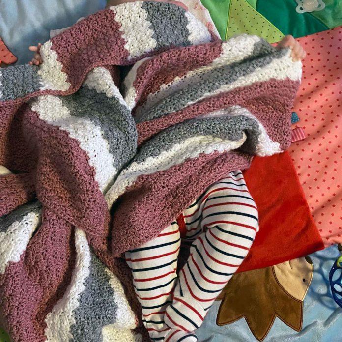 Man sieht unter einer Decke zwei Babybeine und zwei kleine Hände an den Seiten.