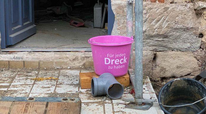 """Eine Baustellensituation, darin in strahlend pinker Eimer mit der Aufschrift """"Für jeden Dreck zu haben""""."""