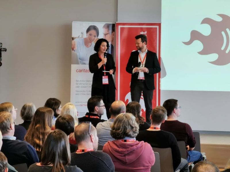 Eine Frau und ein Mann stehen auf einer kleinen Bühne, die Frau spricht gerade in ein Mikrofon.