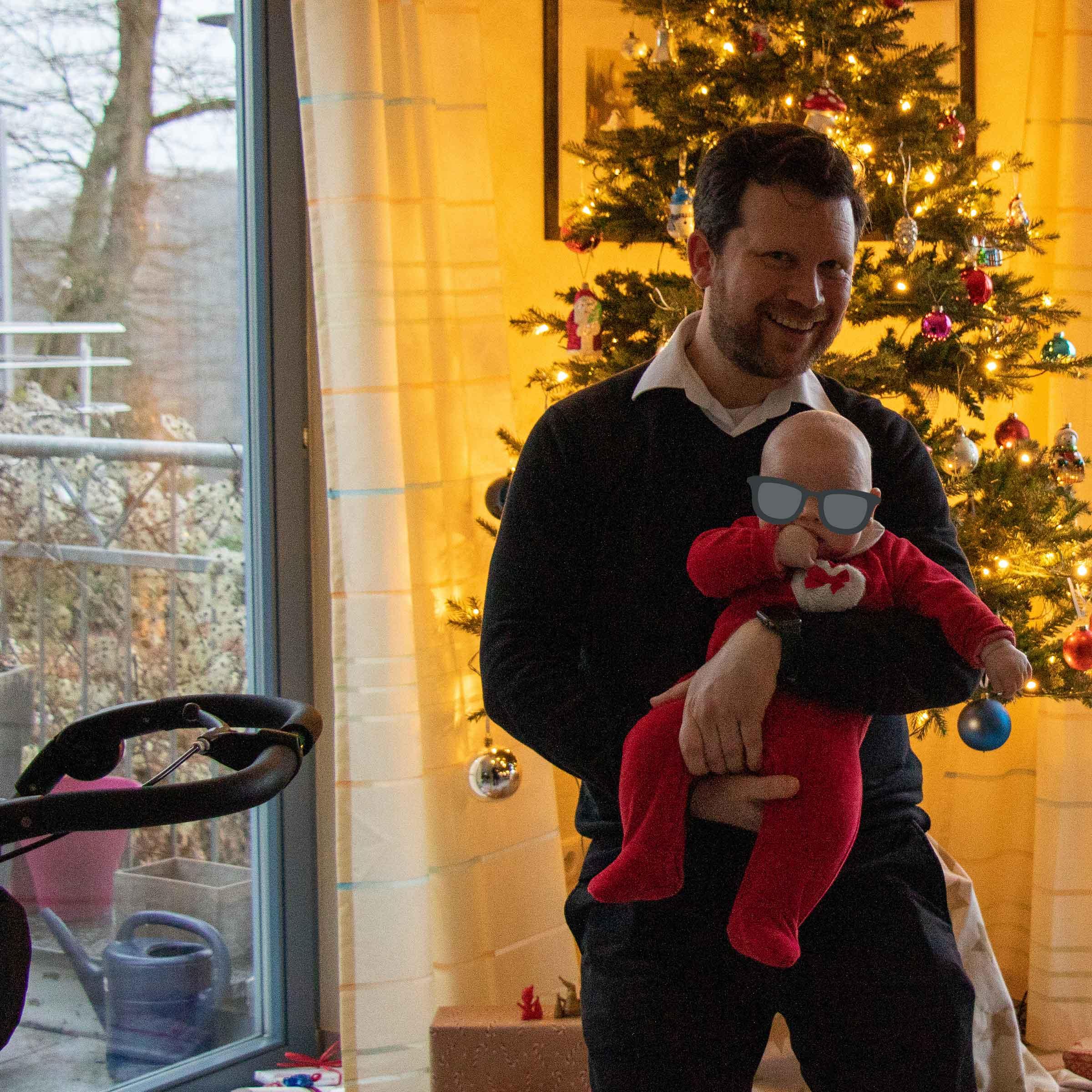 Ein Mann (ich) hält ein Baby (Klein-Lea, roter Strampler mit Schleife auf der Brust), im Hintergrund ein beleuchteter Weihnachtsbaum.