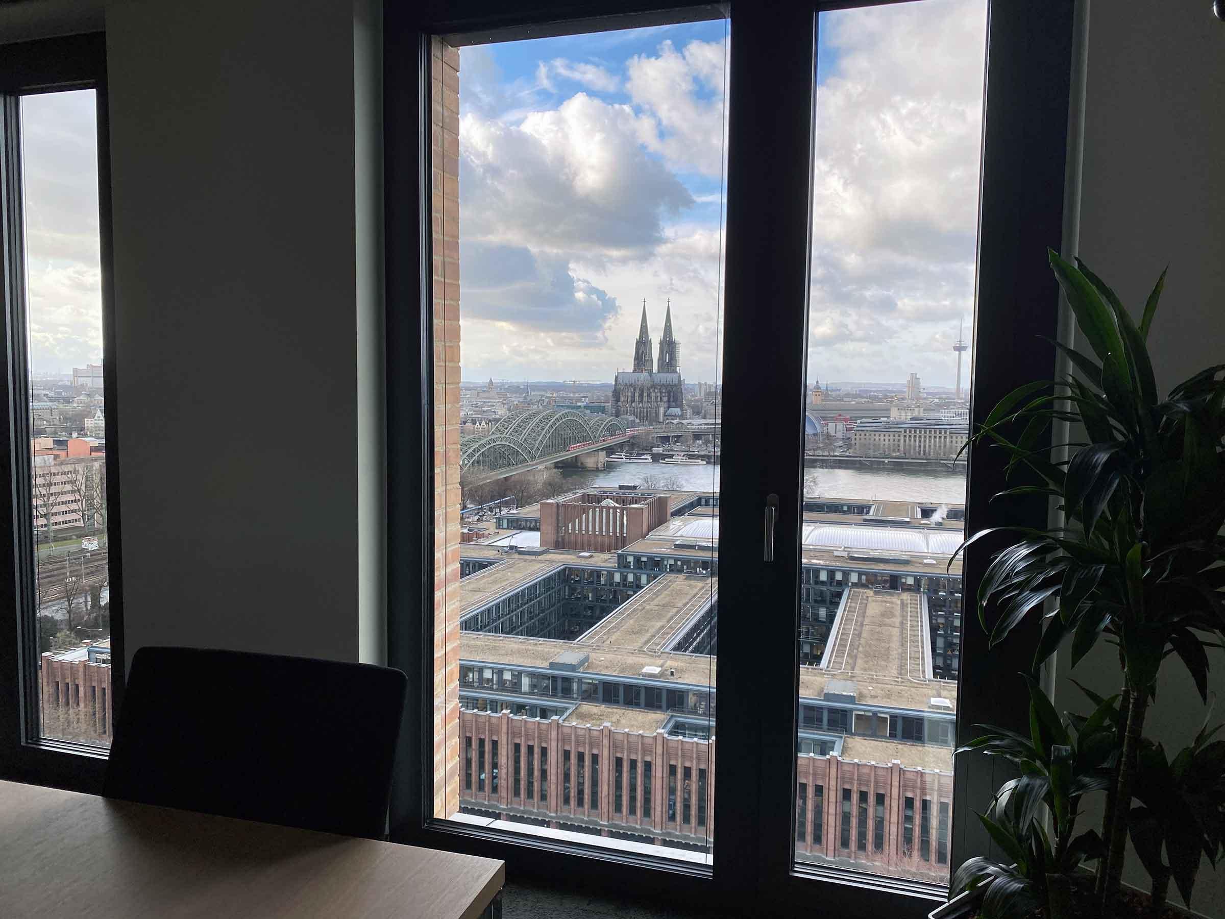 Durch ein Fenster sieht man den Rhein mit Hohernzollernbrücke und Dom. Im Vordergrund erahnt man einen Tisch mit Stuhl sowie eine Zimmerpflanze.