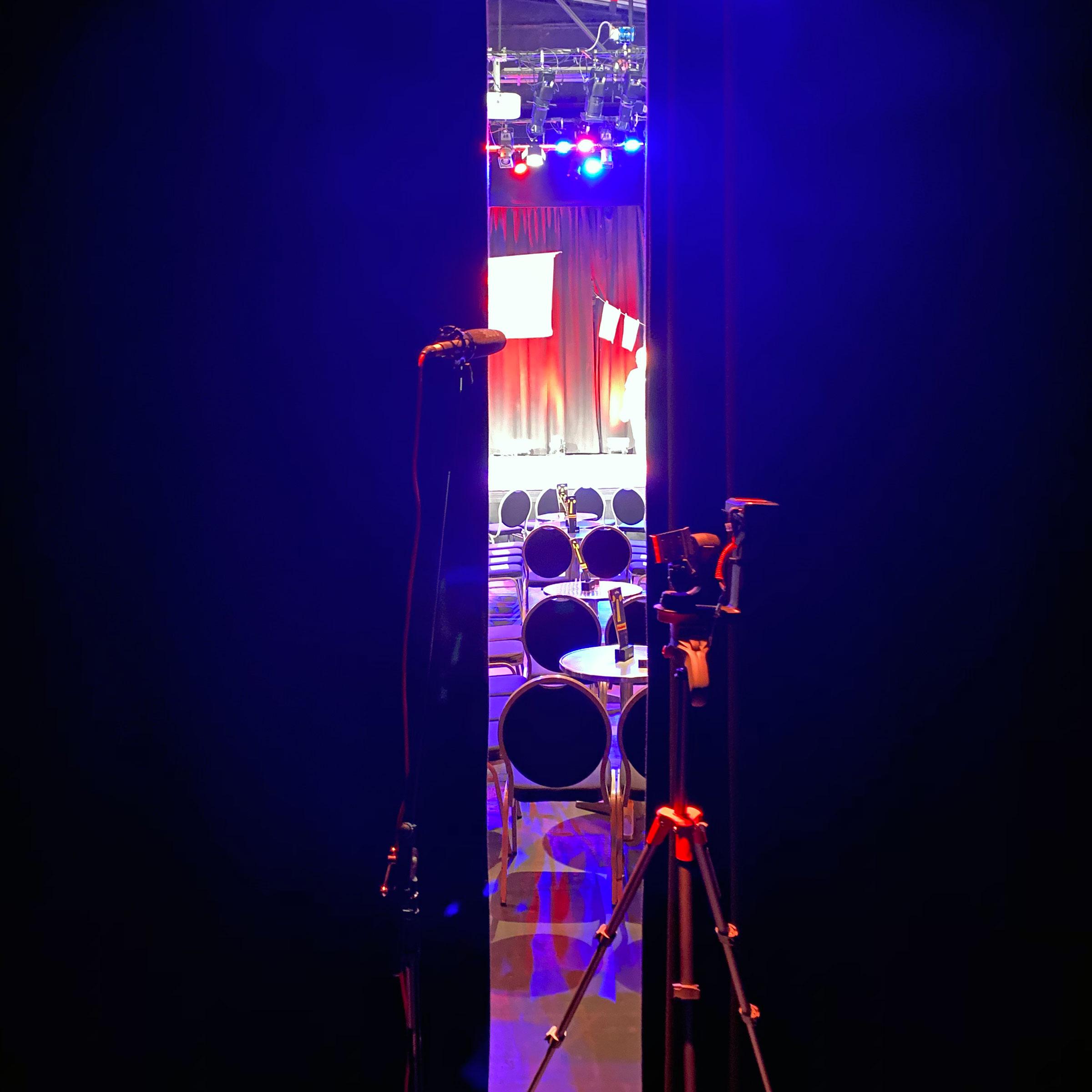 In einem schmalen Schlitz sieht man die Bühne und einige Stühle und Tische. Im Vordergrund zu erahnen sind ein Mikrofon und ein Stativ.
