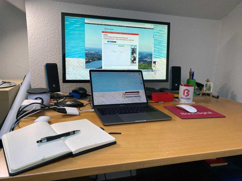 Ein Schreibtisch, darauf ein großer Monitor, davor ein Laptop. Im Bildvordergrund ein Notizbuch mit Stift. Im Hintergrund einige Kabel und eine Bonn.digital-Tasse.