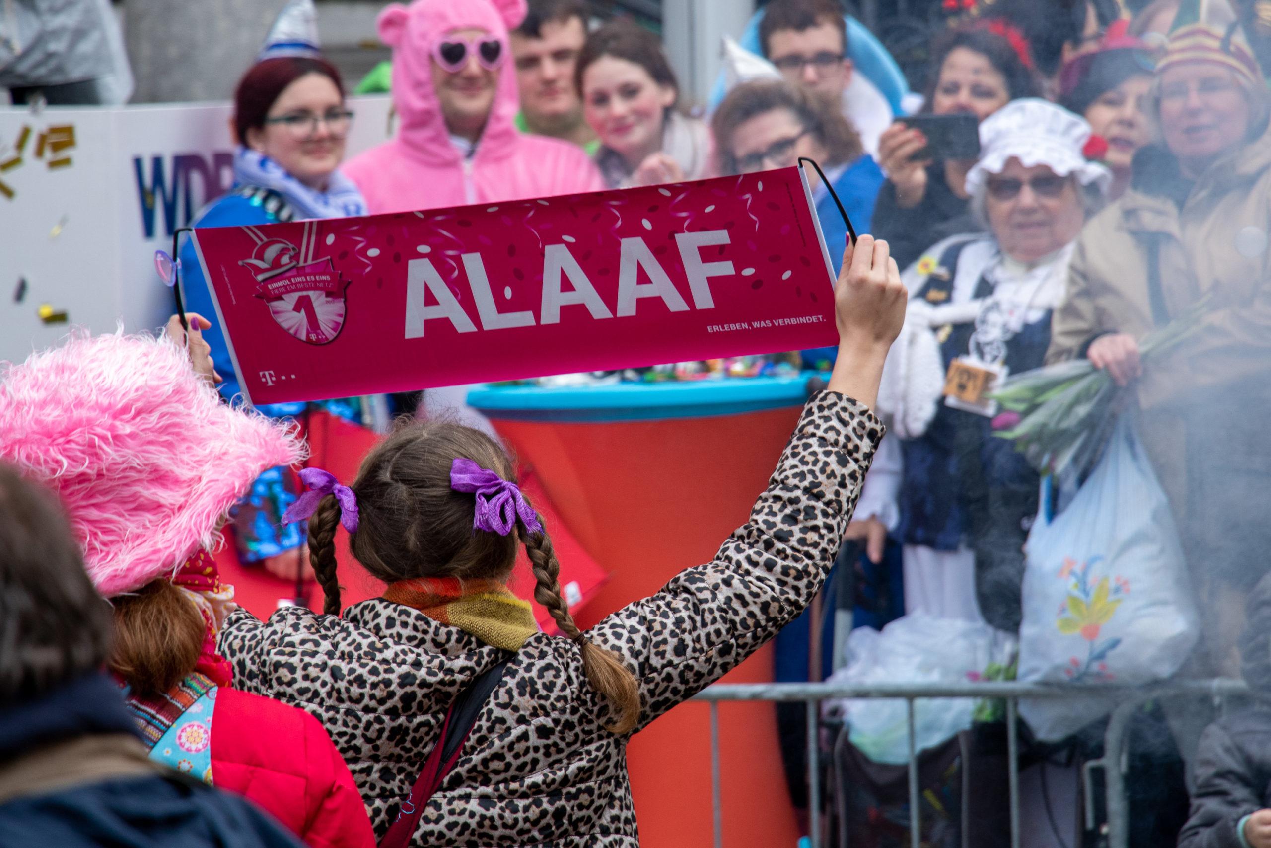 Eine Frau, von hinten fotografiert, hält ein kleines Transparent in die Höhe Richtung verkleidetem Publikum. Aufschrift: Alaaf.