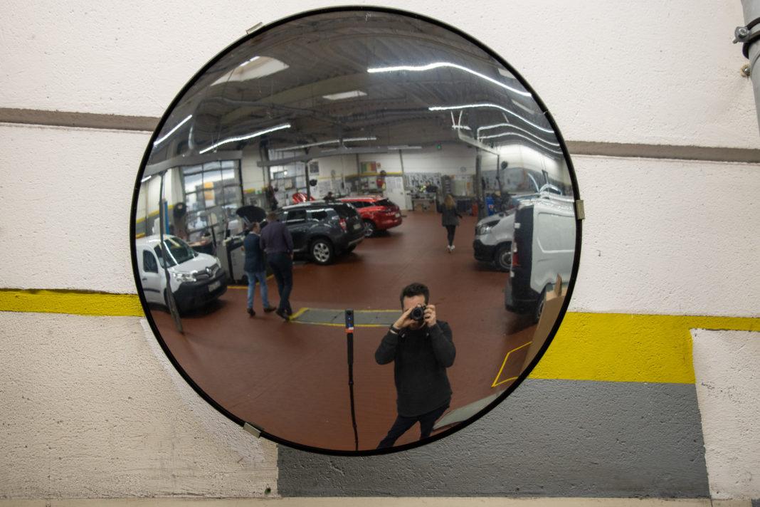 Ich spiegle mich beim Fotografien in einem runden, etwas verzerrenden Spiegel.