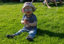 Ein Baby mit Sonnenhut sitzt auf einer grünen Wiese und lächelt.