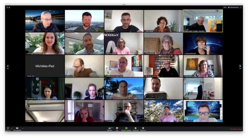 """Screenshot eines Zoom-Calls, man sieht 23 Menschen, ein schwarzes Rechteck mit der Aufschrift """"Michèles iPad"""" und ein Dachfenster."""