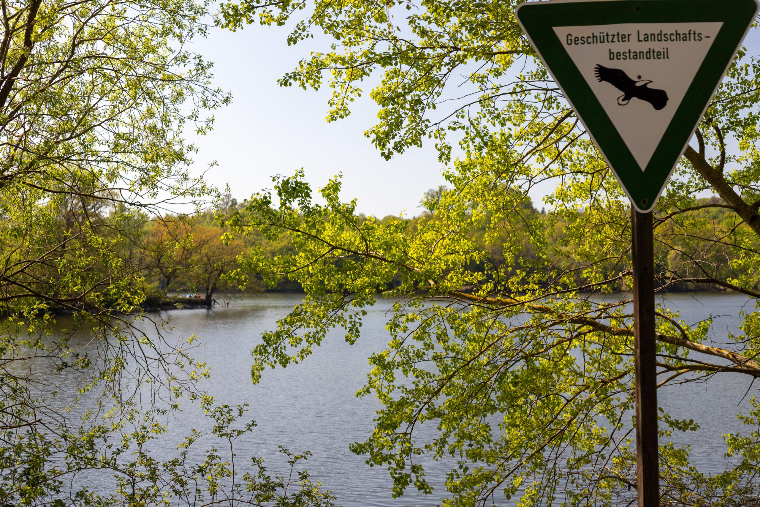 """Blick durch Äste auf den See. Im Hintergrund sind klein auf einer Landzunge Menschen erkennbar. Im Vordergrund ein dreieckiges, auf der Spitze stehendes, grün eingerahmtes Schild mit einem Adler und der Beschriftung """"Geschützter Landschaftsbestandteil"""" darauf."""