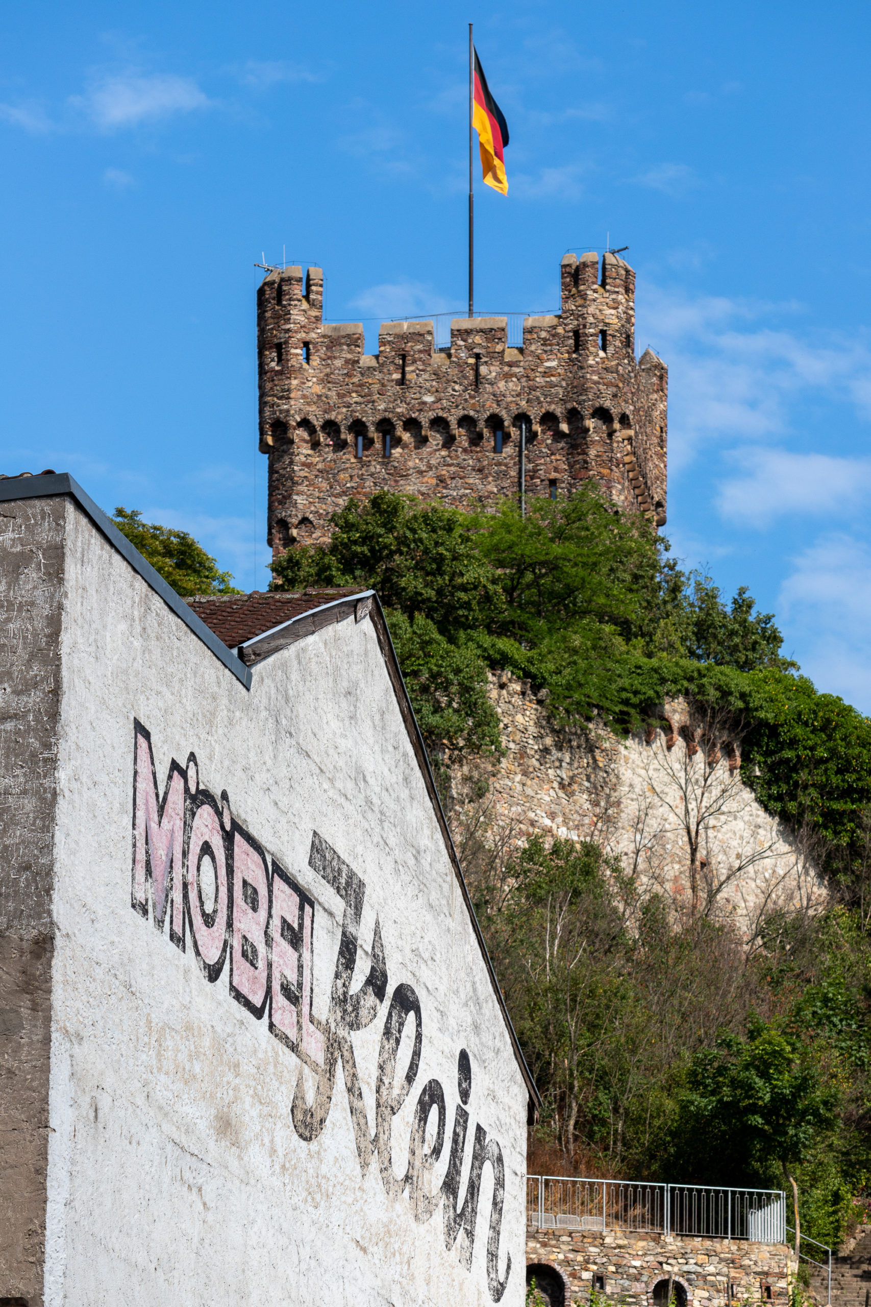 """Im Vordergrund eine Häuserwand, auf der verblichen """"Möbel Klein"""" steht, dahinter der Turm der Turm der Burg Klopp."""