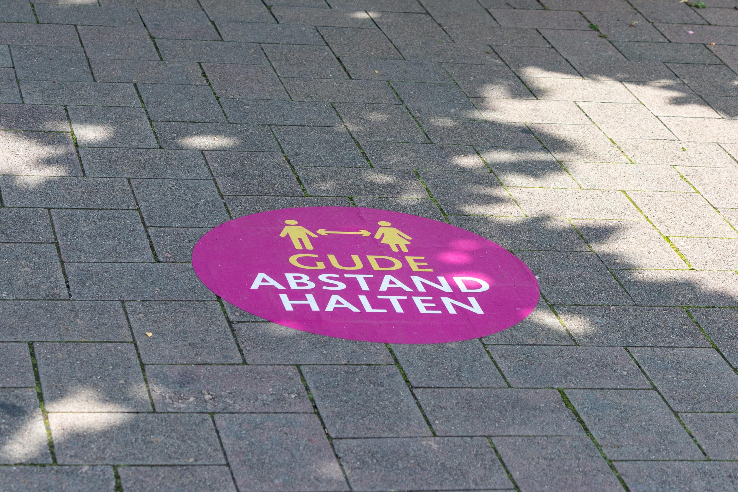 """Ein magentafarbener Kreis ist auf dem Boden geklebt, darauf zwei Menschensymbole mit Abstandspfeil dazwischen, darunter die Worte """"Guden Abstand halten""""."""