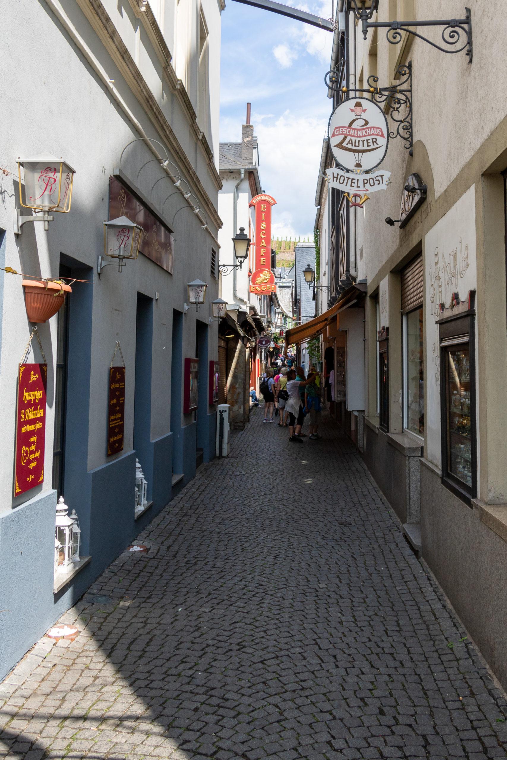 Eine enge Gasse, man sieht Schilder von Geschäften, zum Beispiel das Hotel Post.