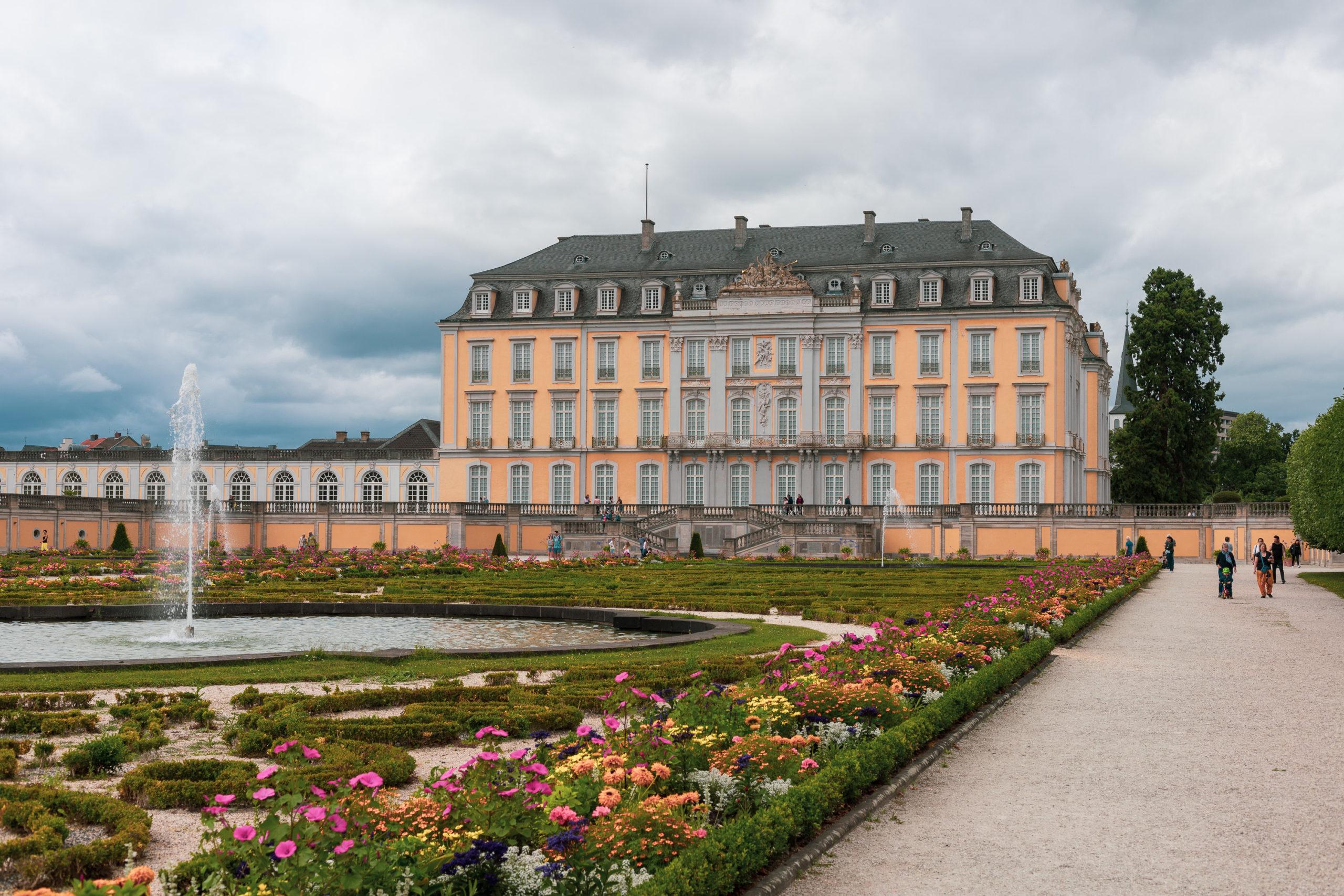 Ein großes, kaisergelbes Schloss mit vier Stockwerken (aber ohne Türme). Davor ein opulenter Garten mit allerlei bunten Blumen und einem großen Springbrunnen.