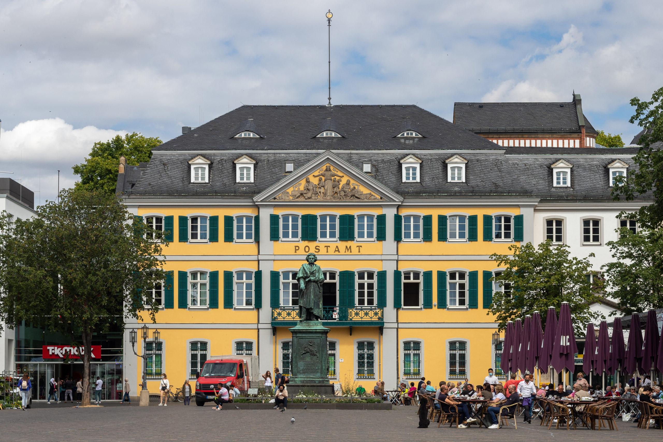 Der Bonner Münsterplatz mit der Beethovenstatue und dem Postamt dahinter. Man sieht rechter Hand viele Menschen im Kaffee sitzen.