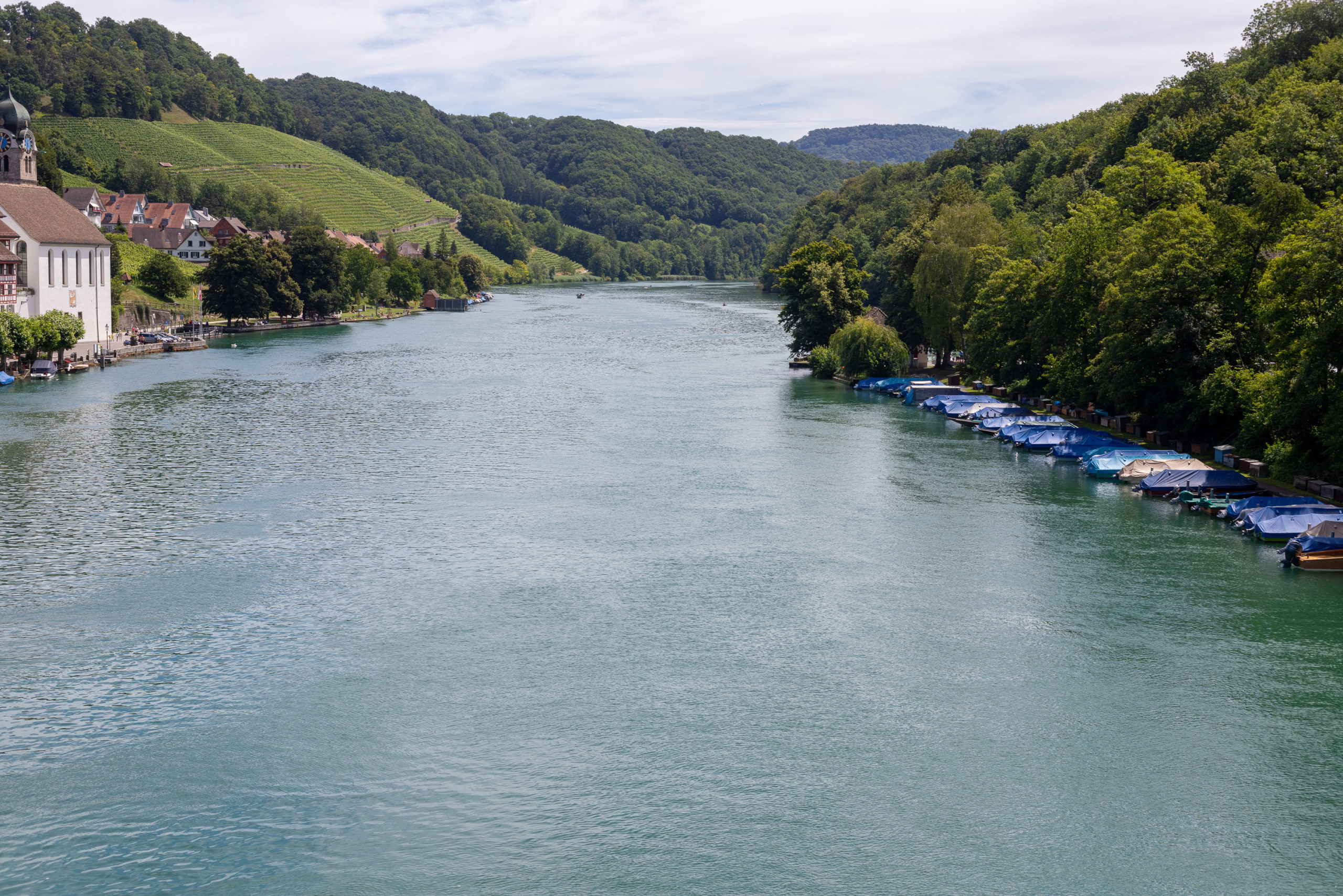 Blick von einer Brücke auf den breiten Rhein, rechts gesäumt von Wäldern, am Ufer Boote. Links auch viel grün, eine Kirche und einige Häuser scheinen durch.