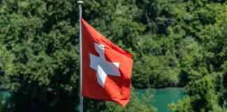 Eine Schweizer Flagge (weißes Kreuz auf rotem Grund) an einem Fahrenmast.