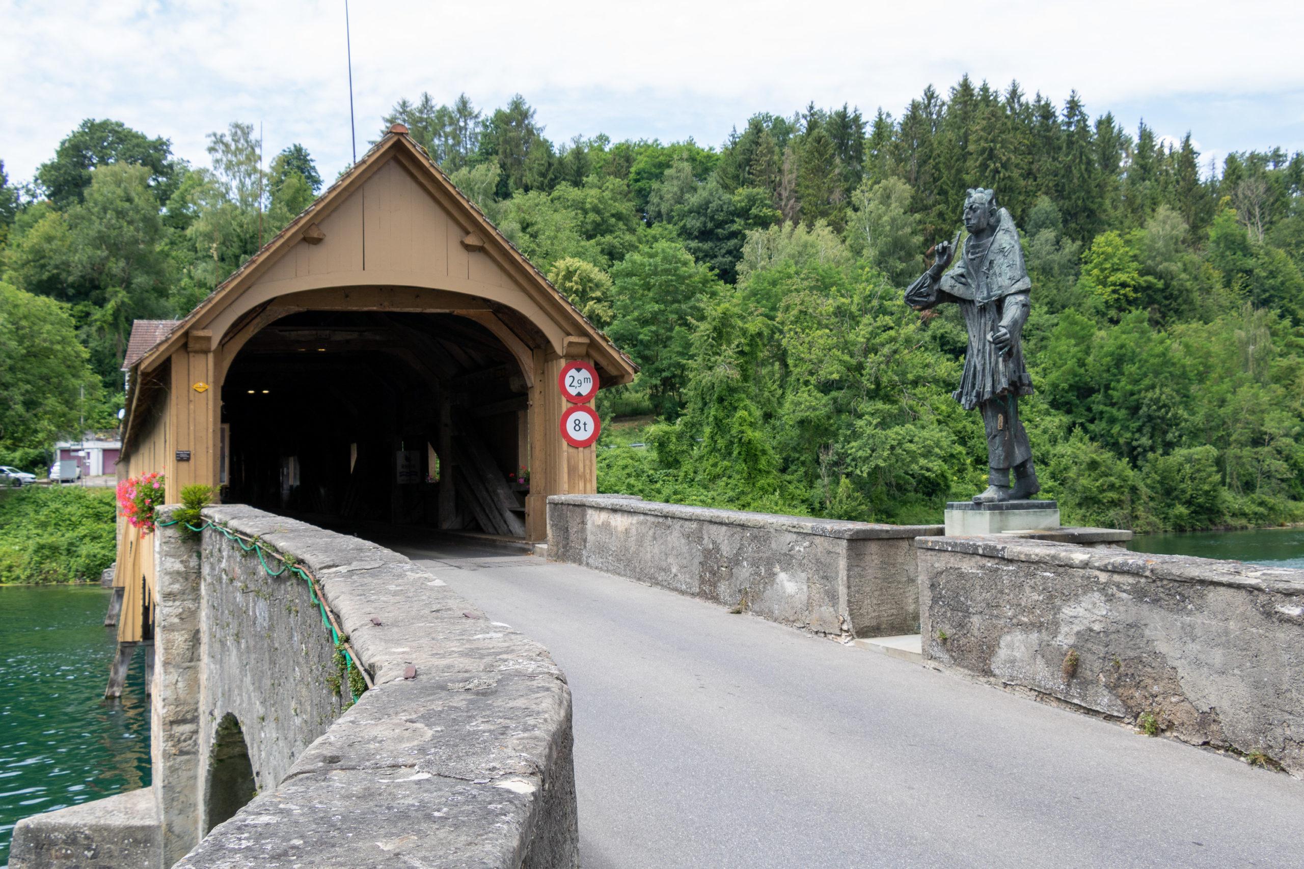 Eine Brücke, die überdacht ist und aussieht wie ein kleines Haus, durch das man hindurchfahren kann. Davor steht rechts noch eine Statue eines unbekannten Manns.