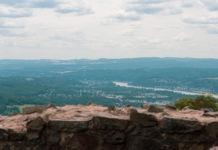 Im Vordergrund ein Stück Mauer, der Fernblick geht auf Hügel und den Rhein.