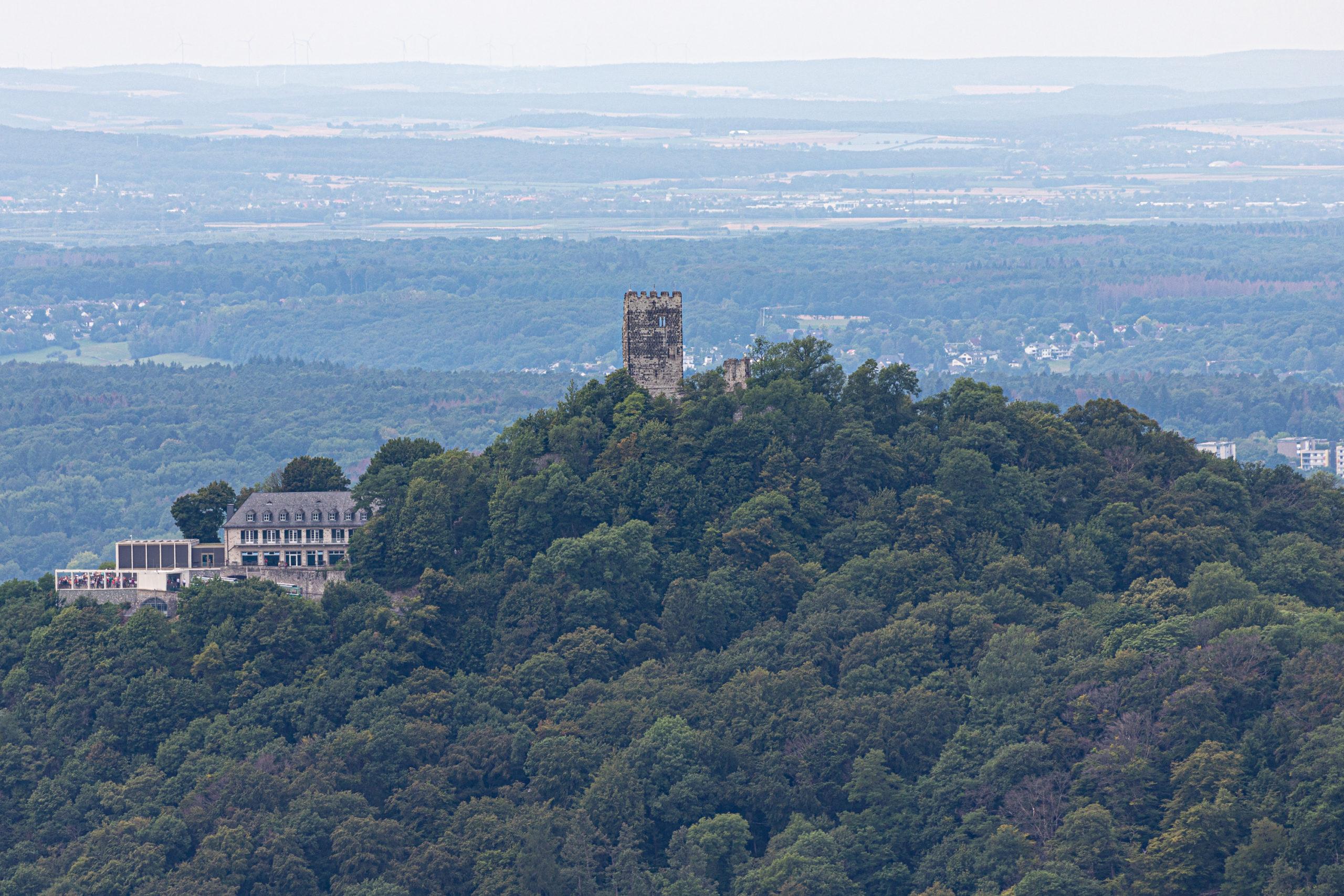 Ein dicht bewachsener Hügel, auf der Spitze ein alter Turm, etwas darunter links ein Haus mit Wintergarten.