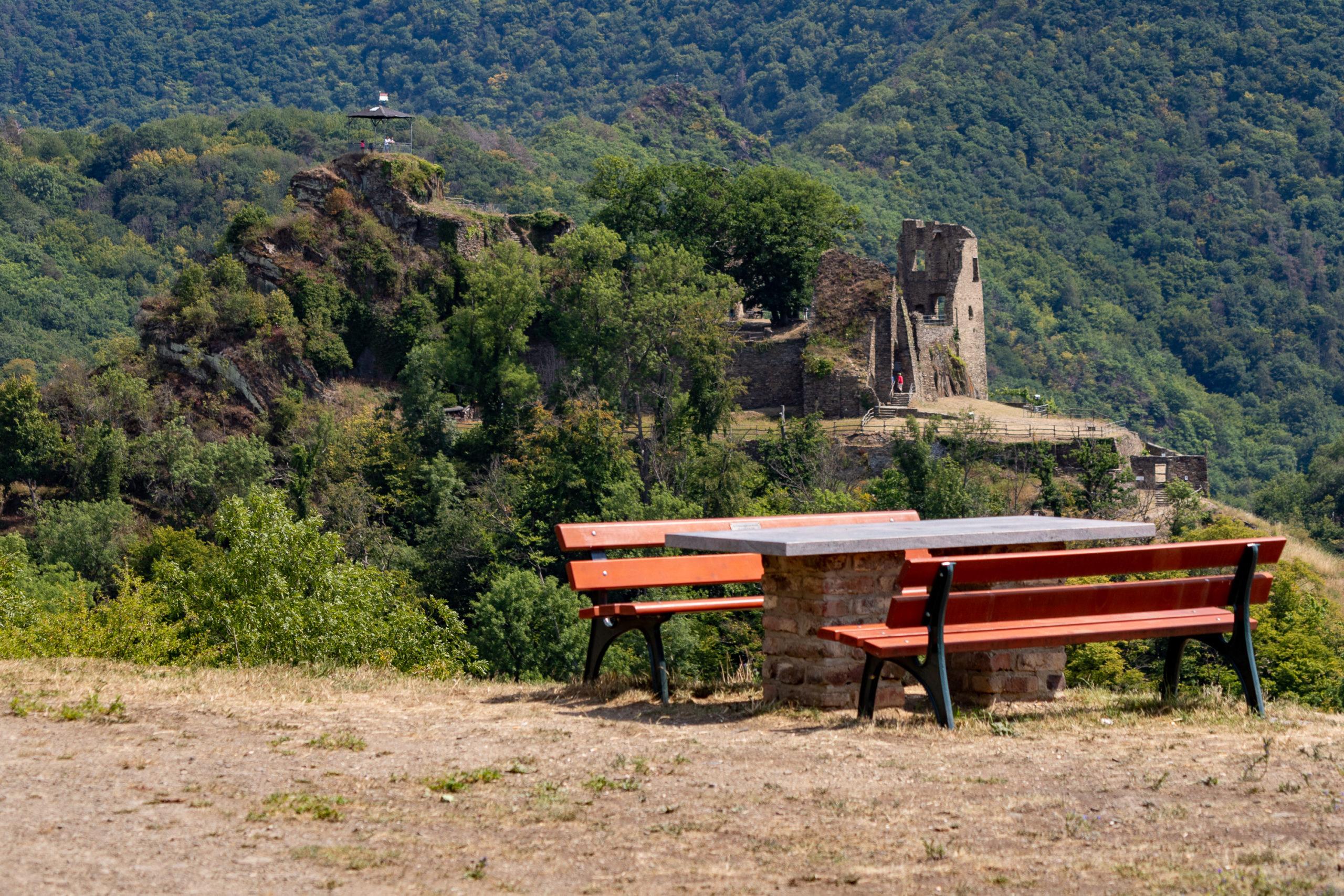 Im Vordergrund ein gemauerter Tisch und zwei Bänke als Sitzgruppe, im Hintergrund, von einem Tal getrennt, eine Burgruine. Rundherum viel Baumgrün.