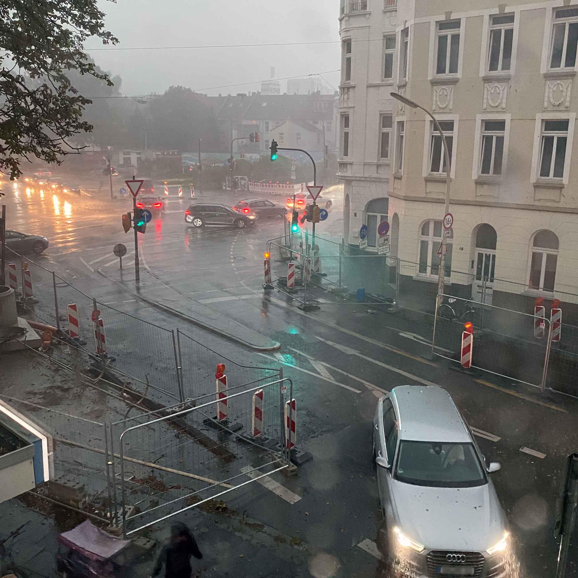 Eine Straßenkreuzung mit einen Autos, dazu Baustellenabsperrungen. Man sieht deutlich, dass es sehr stark regnet.