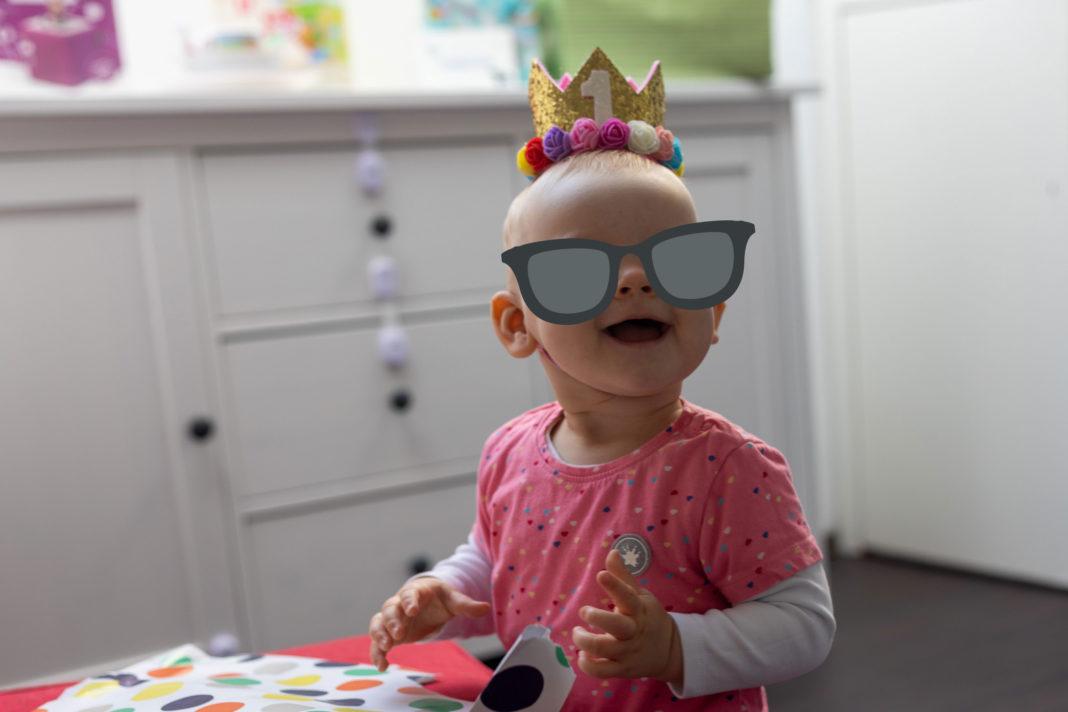 Ein Kind mit rosafarbenem Oberteil steht an einem Hocker und lacht eine Person außerhalb des Bildes an. Auf dem Kopf trägt es eine kleine Krone mit einer 1 darauf.