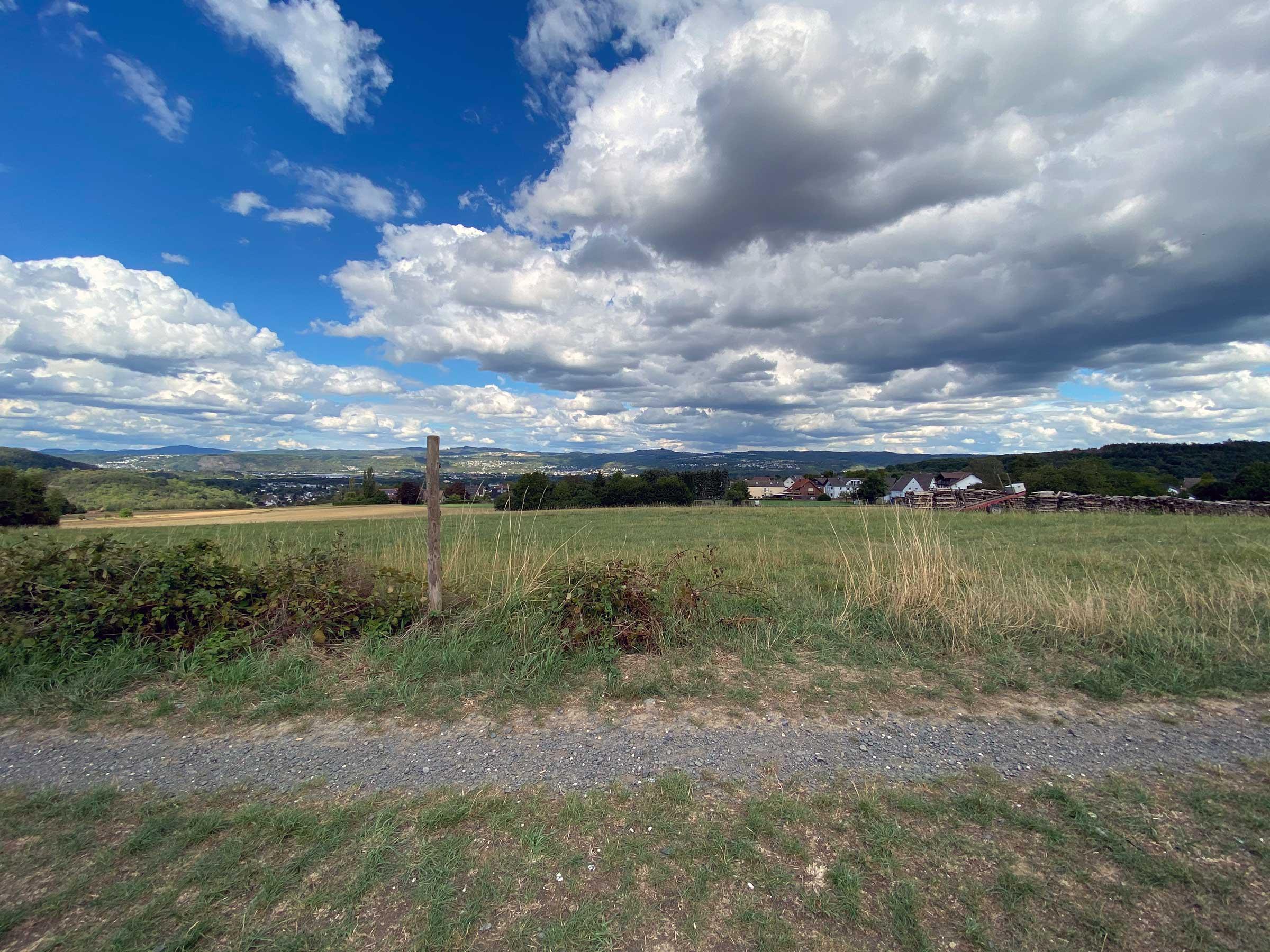 Eine Landschaftsaufnahme. Oben viel Himmel mit großen Wolken, unten viel Wiese auf einer hügeligen Landschaft. Am Horizont sieht man ein paar Häuser.