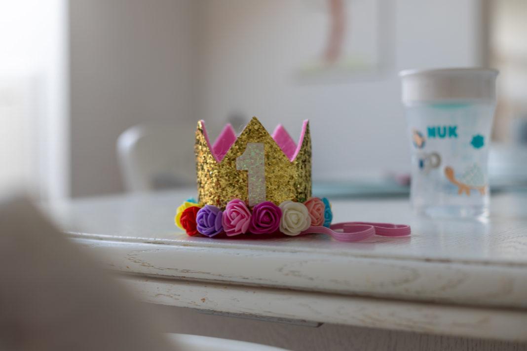 Auf dem Tisch liegt eine kleine Krone mit einer großen 1 darauf. Im Hintergrund ein Trinkbecher für Kleinkinder.