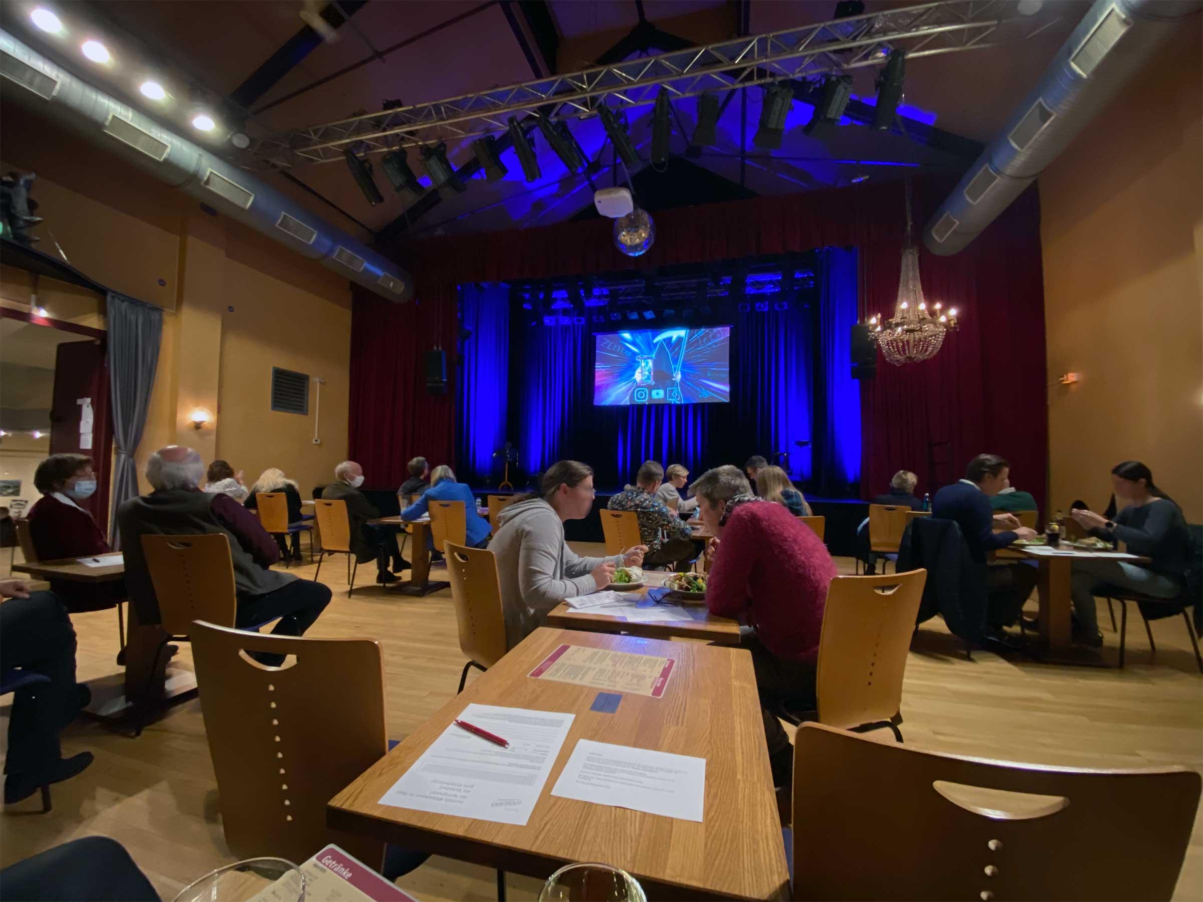 Man sieht einen kleinen Saal mit einigen Tischen und Menschen daran, viele von ihnen essen. Direkt vor dem Fotografen ist ein leerer Tisch, links und rechts leere Stühle. Am Ende des Saals eine blau beleuchtete Bühne.