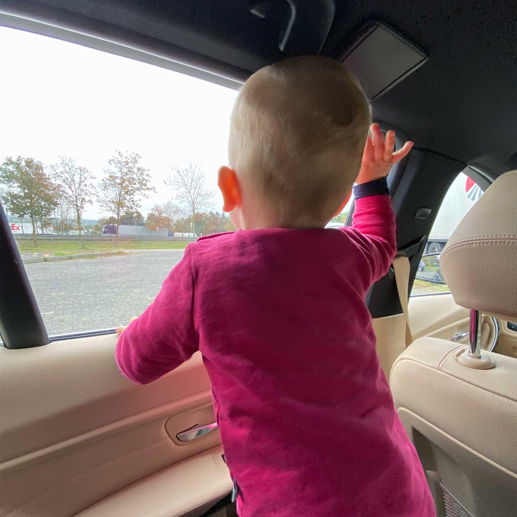 Ein Kind steht auf dem Rücksitz und blickt durch das Seitenfesnter auf die vorbeilaufende Autobahn. Es winkt mit dem rechten Arm den Lastwagen zu.