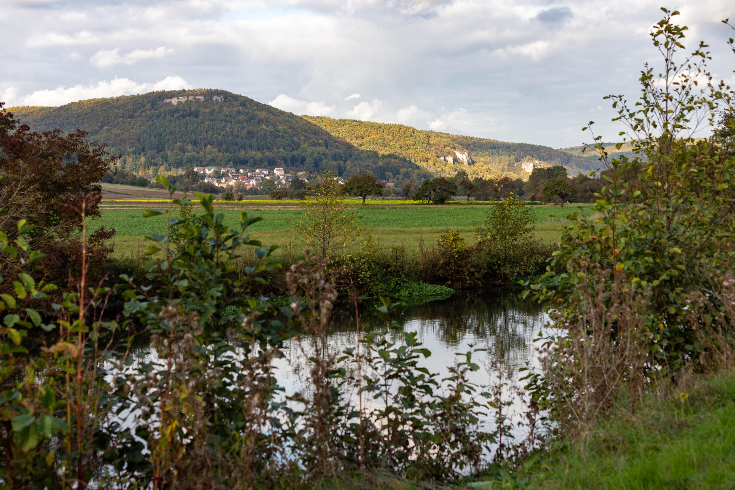 Im Vordergrund ein Bach, dahinter Wiese, dahinter sich sanft aufschwingende Hügel, die teilweise von der Sonne beschienen werden. Am Fuße eine Ortschaft.