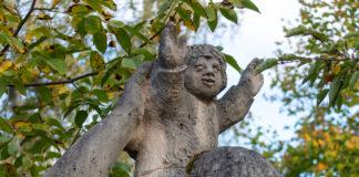 Statue eines Mannes, der ein Kind auf seinen Schultern trägt. Das Kind scheint sich zu freuen, der Mann eher nicht.