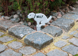 """Ein Aufsteller eines kackenden Hundes, auf dem groß """"No!"""" geschrieben steht."""